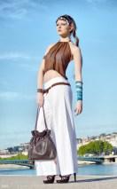 Top dos-nu en mousseline marron, pantalon ample en lin blanc et sa ceinture marron, sac à main marron