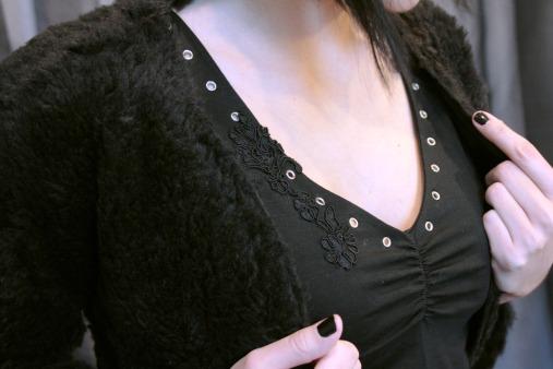 Top en jersey noir, dentelle noire et oeillets argentés, boléro fourrure fantaisie noire